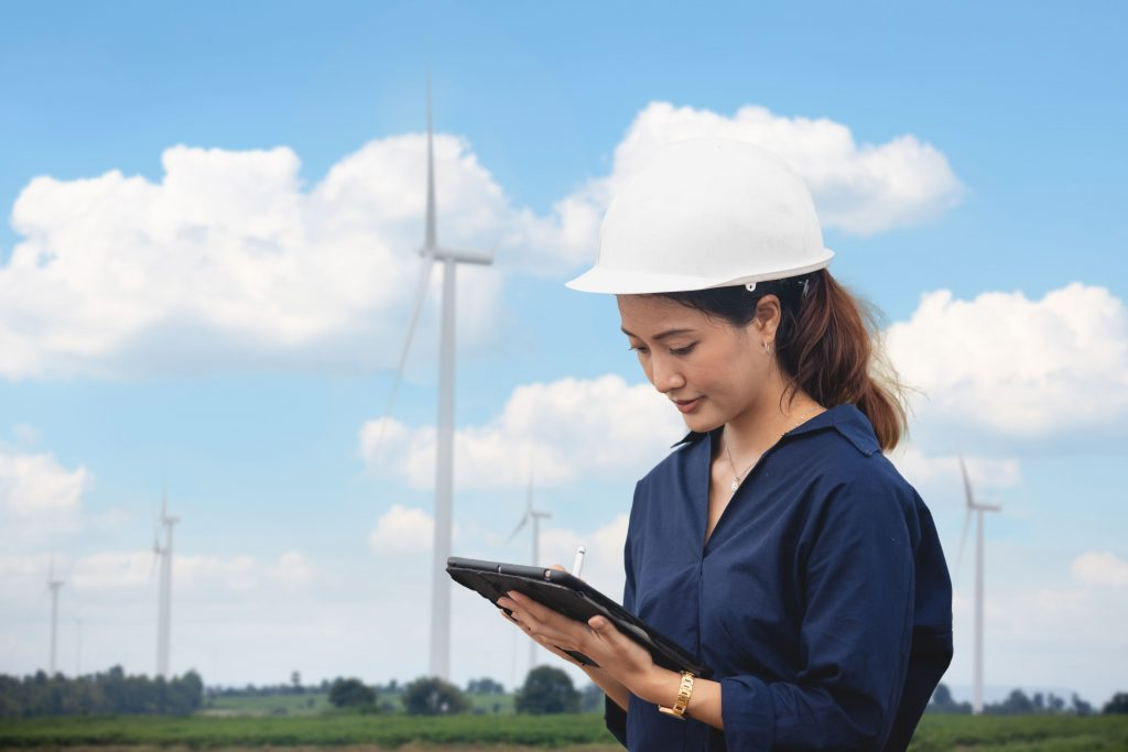 woman standing in front of wind turbines
